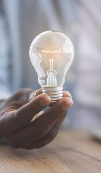 New idea concept. Unrecognizable black businessman holding illuminated light bulb in hand while sitting at workplace in office